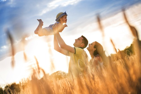 woman in field: Happy pregnant family with little daughter spending time together in sunny field Stock Photo