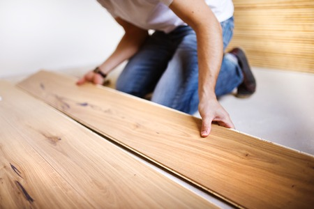 Unrecognizable handyman installing wooden floor in new house