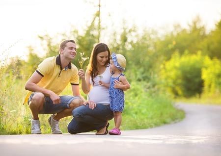 Gelukkig zwangere familie met weinig dochter tijd samen doorbrengen in de zomer de natuur