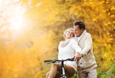 Actieve senior paar samen genieten van romantische wandeling met fiets in de gouden herfst park