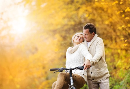 Active senior couple together enjoying romantic walk with bicycle in golden autumn park photo