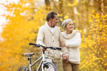 active woman: Active senior couple together enjoying romantic walk with bicycle in golden autumn park