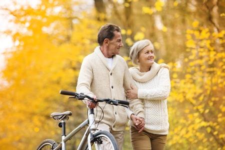 an elderly person: Activos superiores pareja juntos disfrutando de paseo rom�ntico con la bicicleta en el parque de oto�o de oro Foto de archivo