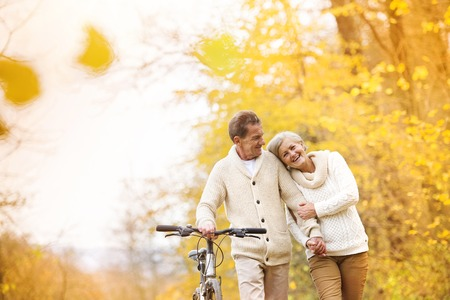 happy senior couple: Active senior couple together enjoying romantic walk with bicycle in golden autumn park