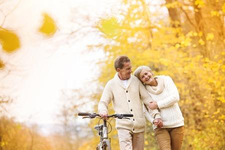 tercera edad: Activos superiores pareja juntos disfrutando de paseo rom�ntico con la bicicleta en el parque de oto�o de oro Foto de archivo