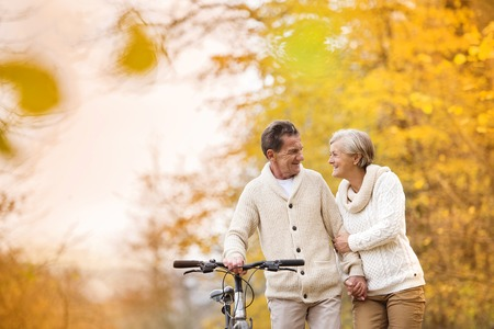 Active senior couple together enjoying romantic walk with bicycle in golden autumn park