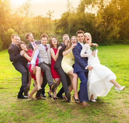 bridesmaids: Full length portrait of newlywed couple having fun with bridesmaids and groomsmen in green sunny park Stock Photo