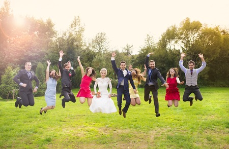 Full length portrait of newlywed couple with bridesmaids and groomsmen jumping in green sunny park Stock Photo