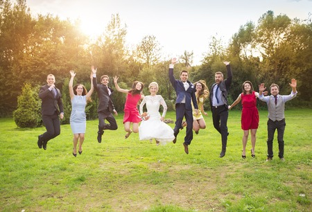 group picture: Full length portrait of newlywed couple with bridesmaids and groomsmen jumping in green sunny park Stock Photo