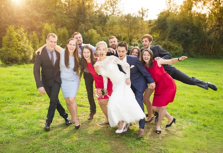 Full length portrait of newlywed couple having fun with bridesmaids and groomsmen in green sunny park Stock Photo