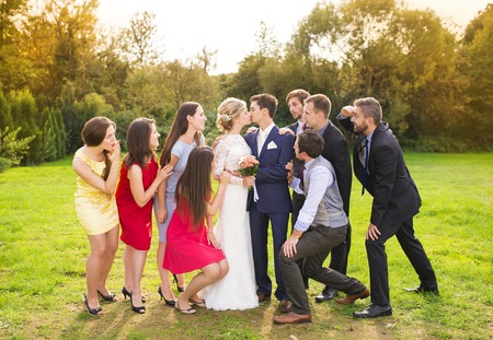 formal party: Full length portrait of newlywed couple kissing posing with bridesmaids and groomsmen in green sunny park