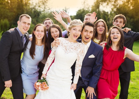 group picture: Portrait of newlywed couple having fun with bridesmaids and groomsmen in green sunny park