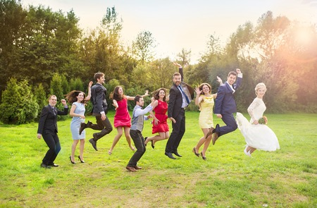 jump suit: Full length portrait of newlywed couple with bridesmaids and groomsmen jumping in green sunny park Stock Photo