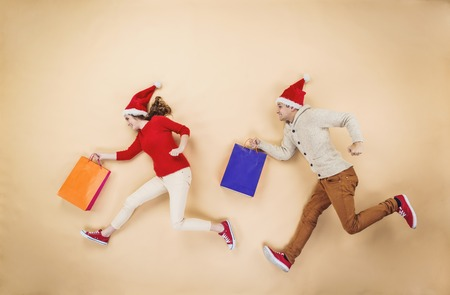 Young couple in Christmas hats having fun running with shopping bags against the beige background Foto de archivo