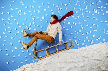 sledging people: Happy young man on sled having fun against the blue background with snowflakes