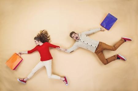 gente loca: Joven pareja en sombreros de la Navidad que se divierten corriendo con bolsas de la compra contra el fondo beige Foto de archivo