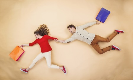 Young couple in Christmas hats having fun running with shopping bags against the beige background Banque d'images