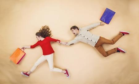comprando: Joven pareja en sombreros de la Navidad que se divierten corriendo con bolsas de la compra contra el fondo beige Foto de archivo