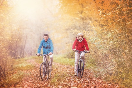 active couple: Active seniors ridding bike in autumn nature. They relax outdoor.