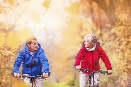 Active seniors ridding bike in autumn nature. They relax outdoor. photo