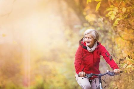 senior health: Active senior woman ridding bike in autumn nature.