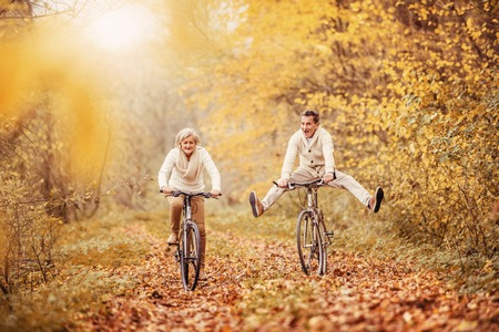 Active seniors ridding bike in autumn nature. They having fun outdoor. Фото со стока