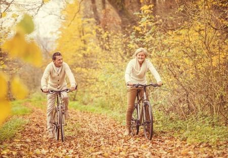 Active seniors ridding bike in autumn nature. They having fun outdoor. photo