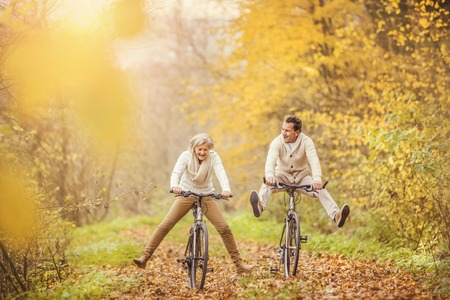 Active seniors ridding bike in autumn nature. They having fun outdoor. Stock fotó