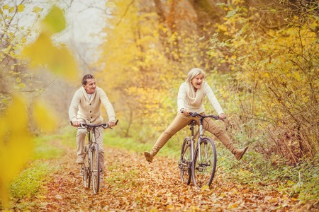Active seniors ridding bike in autumn nature. They having fun outdoor. photo