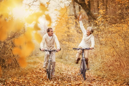 Active seniors ridding bike in autumn nature. They having fun outdoor. Imagens