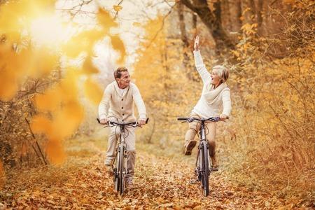 Anziani attivi liberare bici in natura autunnale. Essi divertirsi all'aperto.