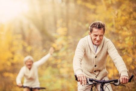 Active seniors ridding bike in autumn nature. They having fun outdoor. Stock Photo