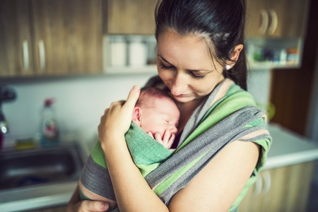 newborns: Newborn baby hold by mother in the baby wrap carrier.
