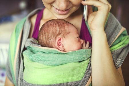 아기 랩 캐리어 어머니에 의해 신생아 유지. 휴대 전화에서 엄마를 호출합니다. 스톡 콘텐츠