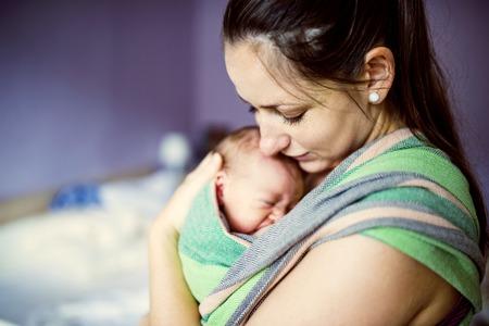 neonato: Asimiento bebé recién nacido por la madre en el portador de envolver al bebé.