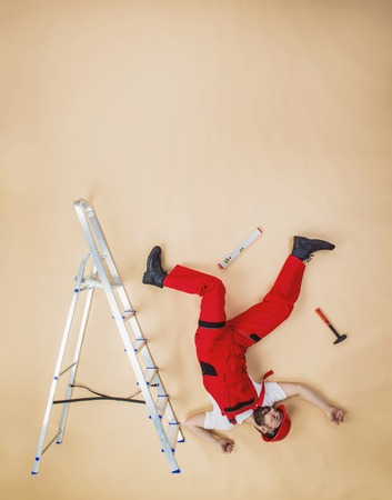 ladder safety: Construction worker have an accident. Funny studio pose. Stock Photo