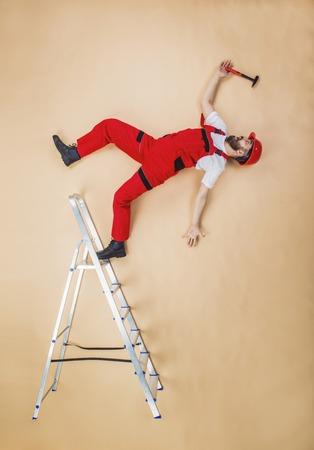 hombre cayendose: Trabajador de la construcción tiene un accidente. Estudio Actitud divertida.