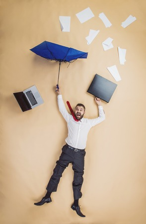 fired manager is falling down with umbrella. Man loses his job. photo