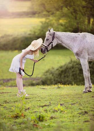 femme et cheval: Femme en robe blanche marche à cheval dans la campagne verte Banque d'images