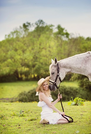 girl on horse: Woman in white dress walking with horse in green countryside