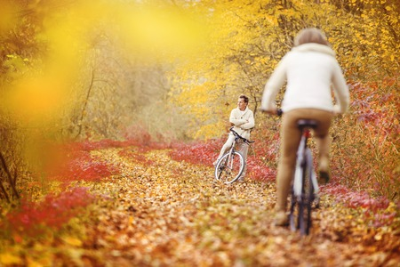 Active seniors riding bike in autumn nature. They relax outdoor. Stock Photo
