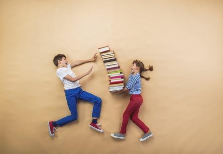 Niños felices jugando con un grupo de libros de estudio Foto de archivo - 34111872