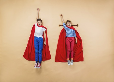 super red: Children are playing as superheroes with red coats