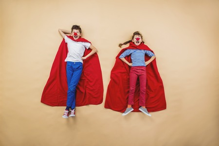 courageous: Children are playing as superheroes with red coats