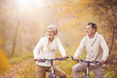Active seniors riding bike in autumn nature. They relax outdoor. Фото со стока