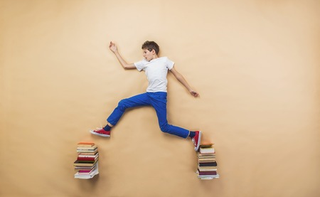 child reading book: Happy boy is playing with group of books in studio
