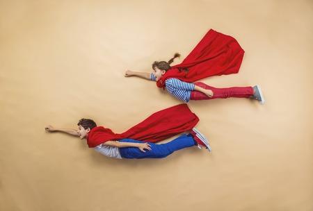 imaginacion: Los niños están jugando como superhéroes con capas rojas