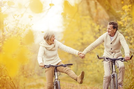 Active seniors riding bike in autumn nature. They relax outdoor. Banco de Imagens
