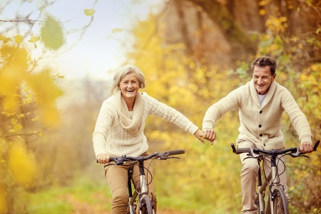Active seniors riding bike in autumn nature. They relax outdoor. Stockfoto