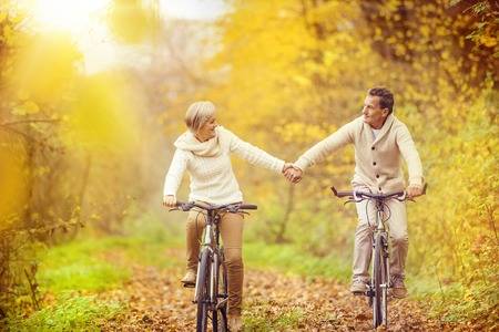 Active seniors riding bike in autumn nature. They relax outdoor. Archivio Fotografico